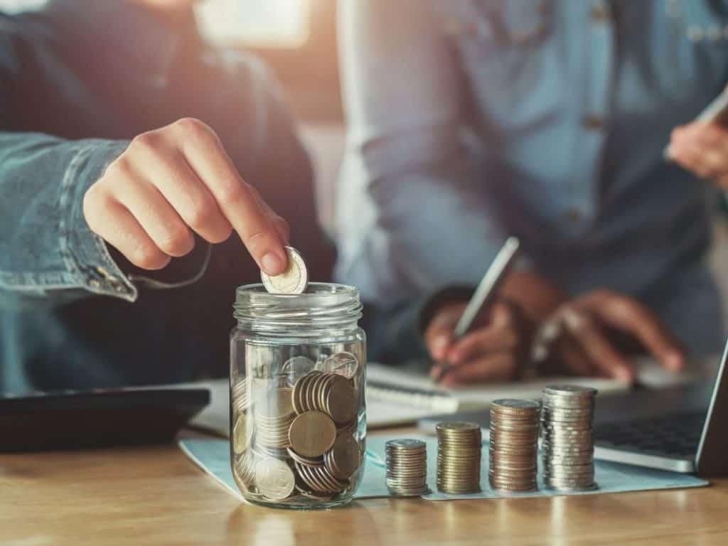 Cómo ahorrar dinero: moneda en una jarra.